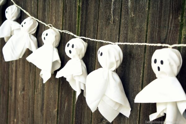this is a super simple halloween diy decoration using a strand of white lantern lights cover each light in white fabric and secure with string or a band