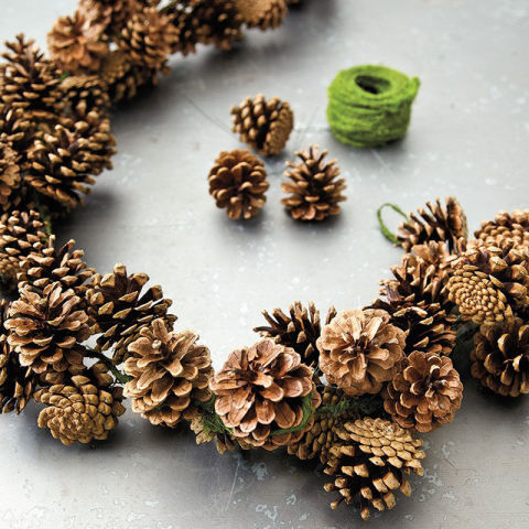 Add a pine cone garland to your mantel and leave it up through the holidays. Find more Thanksgiving decorating ideas here.