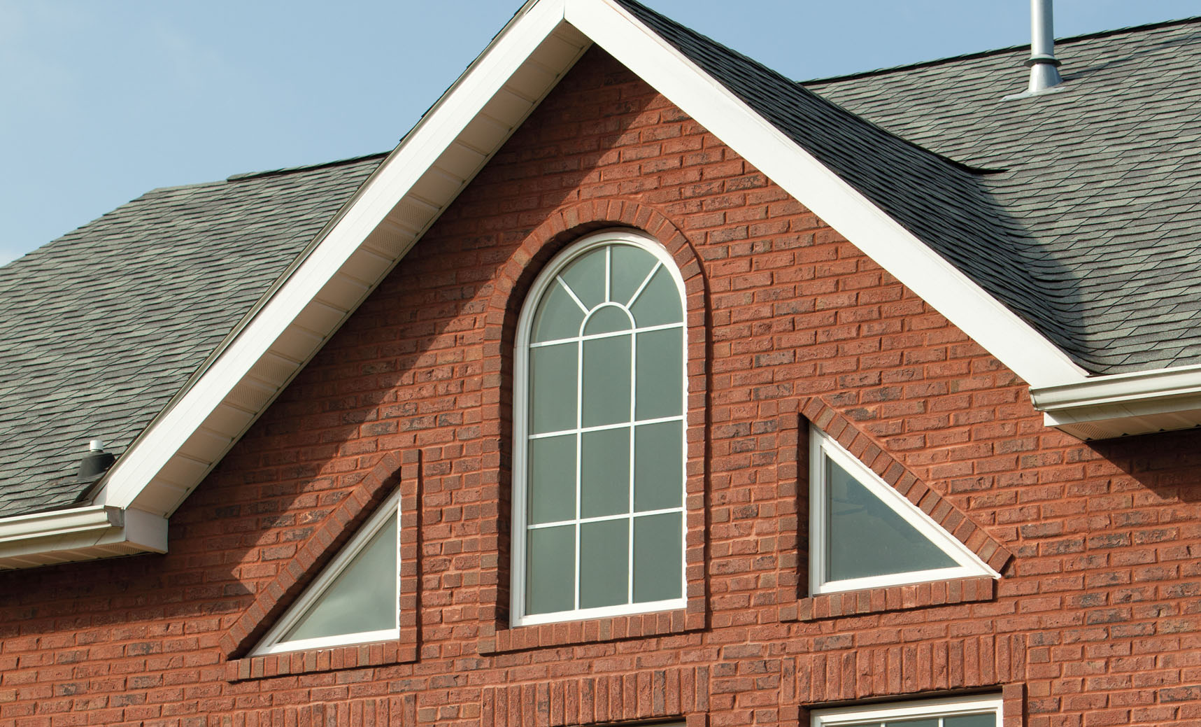 Simonton vinyl replacement geometric windows on brick house