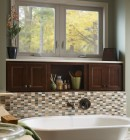 Two awning windows in a bathroom above a tile-lined bathtub