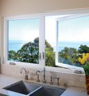 Casement kitchen windows above sink overlooking treeline and ocean
