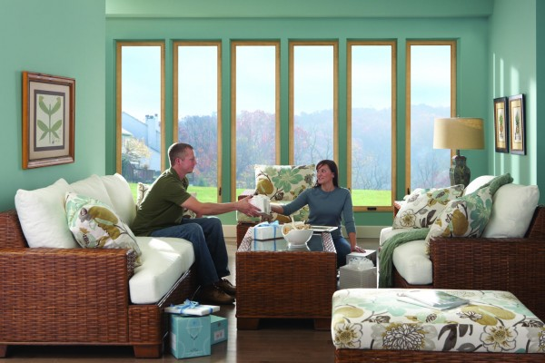 Six tall casement windows in bright teal living room