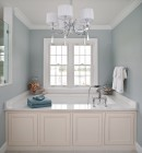 Twin double hung brushed nickel vinyl windows in elegant bathroom above large luxury bathtub