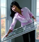 Woman cleaning double hung windows with ease overlooking rolling autumn hills.