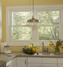 Twin double hung vinyl windows with victorian grid pattern above sink in laundry room brighten up the room