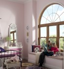 Large geometric seating with window with seating in child's pink bedroom