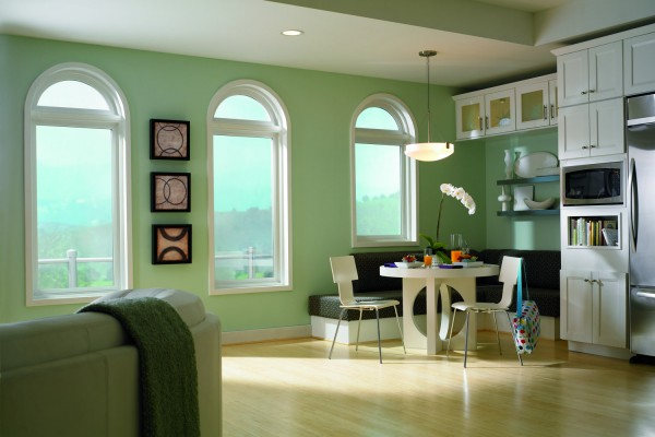 Three geometic picture windows in a light green kitchen/living room.