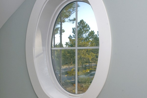 Small circular geometric window in grey wall