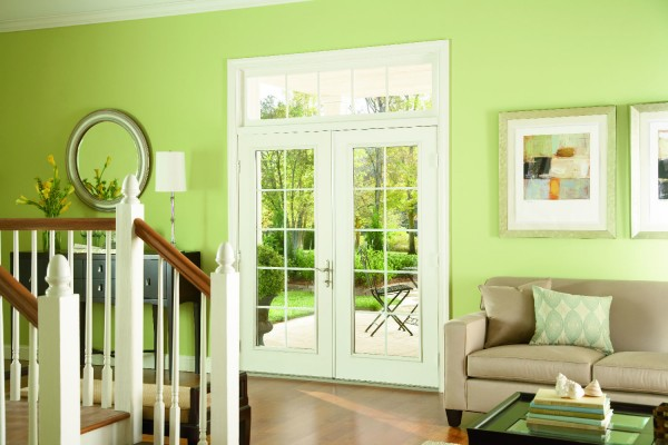 Swinging patio doors in light green living room leading to the backyard patio