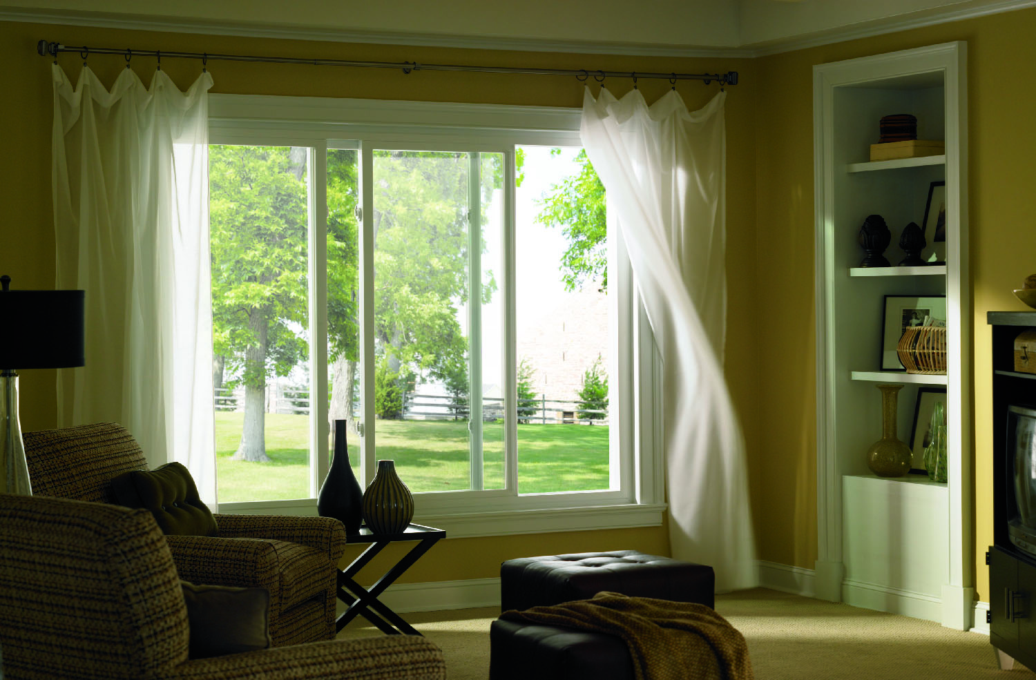 Large slider vinyl windows bring a breeze from outside into living room