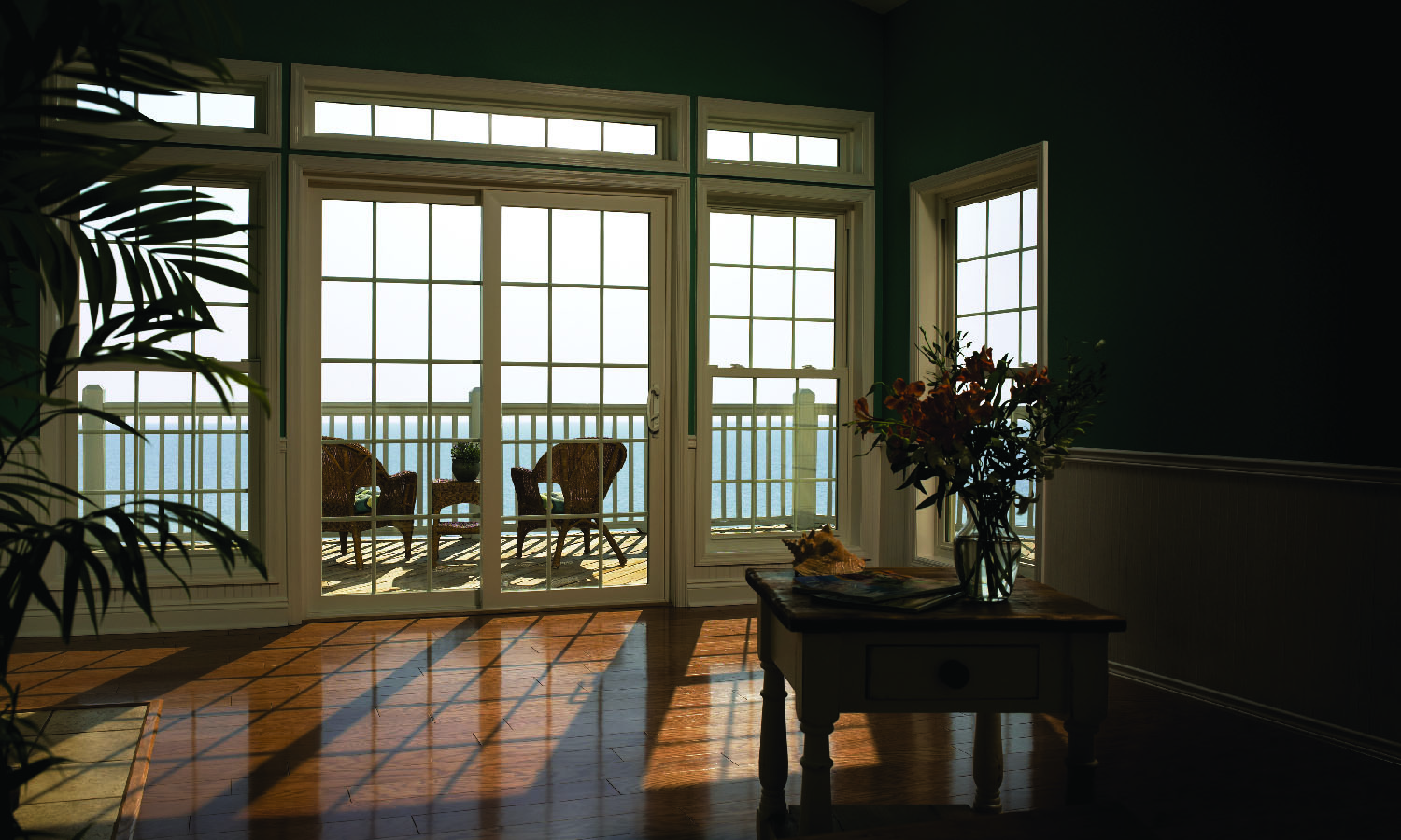 Sliding patio doors are surrounded by double hung windows with colonial grid pattern amplifying space and exterior view