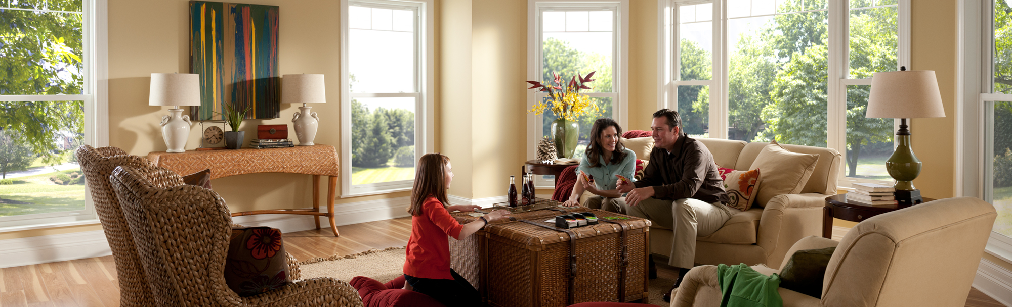Family room with double hung windows with family gathered around coffee table