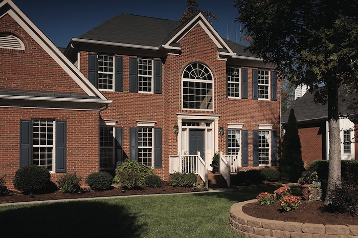 Exterior Front Side View Of Colonial Style Brick House With Several Single Hung Windows